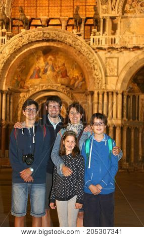cheerful family of tourists with 3 children and mom and dad visiting venice at night
