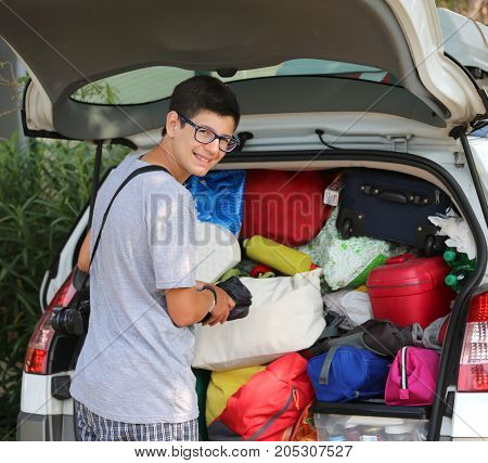 Young Boy With Glasses Puts Suitcases In The Luggage Of The Car