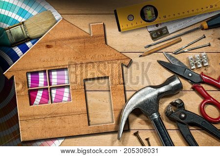 Home improvement concept - Wooden model house on a work table with tools