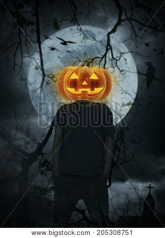 Pumpkin monster head on man body standing over cross church crow birds dead tree full moon and cloudy sky Halloween concept