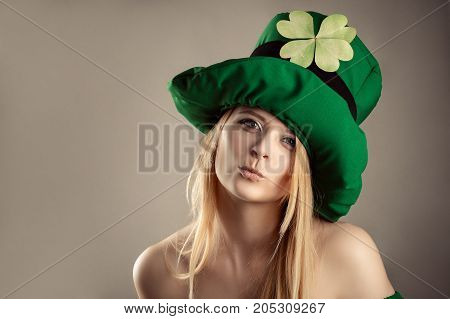 charming blond girl in image of leprechaun with air kiss gesture