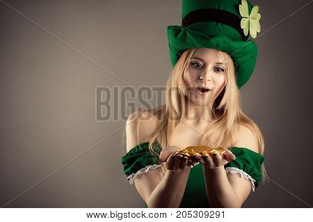 surprised blond girl in image of leprechaun with gold coins in hands