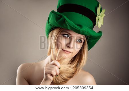 beautiful charming blond girl in leprechaun image isolated on gray background
