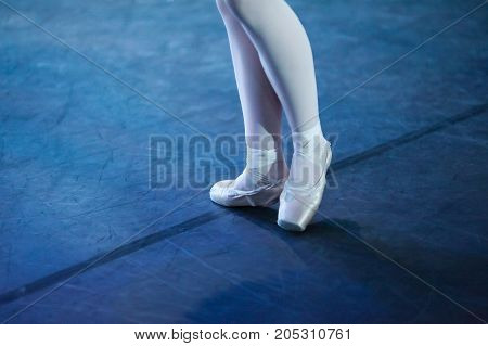 outfit, accessories, ballet concept. light pink pointe shoes has special form for unique feet of girl and two wight ribbons on each legs wrap around her ankles in opposite directions