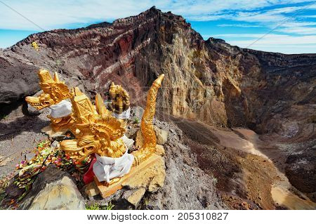 Balinese hindu shrine on brink of volcanic crater with traditional religious offering for volcano spirits protecting against eruption. Summit of active volcano Mount Agung on Bali island Indonesia.