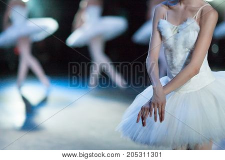 choreography, entertainment, passion concept. close up of long, slender and skinny arms of beautiful female ballet dancer crossed above the white tutu
