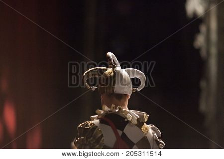 outfit, theater, excitement concept. back of young man dressed in costume of the court jester with funny fools cap and bright jacket with black and gold rhombuses