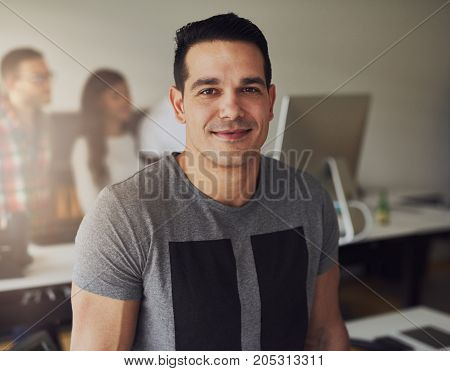 Happy young businessman looking at camera standing in the office.