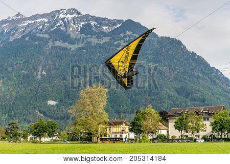 Interlaken Switzerland - May 26 2016: The hang glider lands against the background of the Swiss Alps in Interlaken Switzerland.