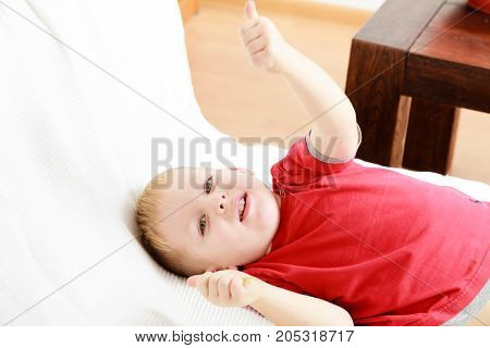 Childhood kids imagination concept. Little young boy playing on sofa and having fun
