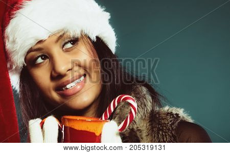 Christmas time concept. Closeup mixed race teen girl wearing santa helper hat holding red mug with hot beverage and striped candy cane studio shot on blue