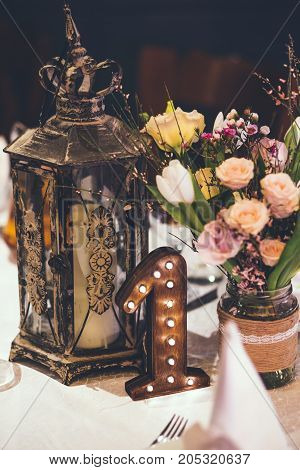 decor on the table with old night lamp, beautiful flowers and number one