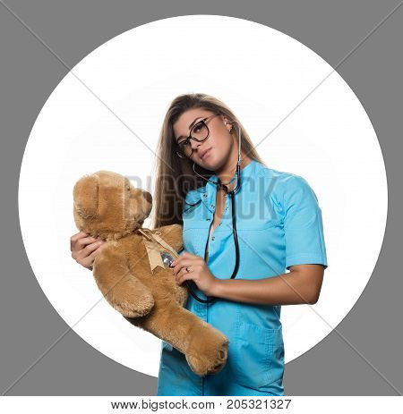 Sexy female doctor with stethoscope heals a teddy bear on a white circle and black background.