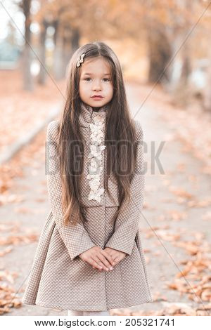 Beautiful child girl 4-5 year old wearing stylish elegant jacket posing over autumn background. Looking at camera. Trendy kids.