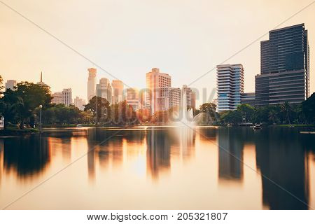 Urban skyline of Bangkok with reflection in the lake waters at the sunset.