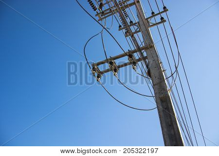 electric pole power lines and wires with blue sky.