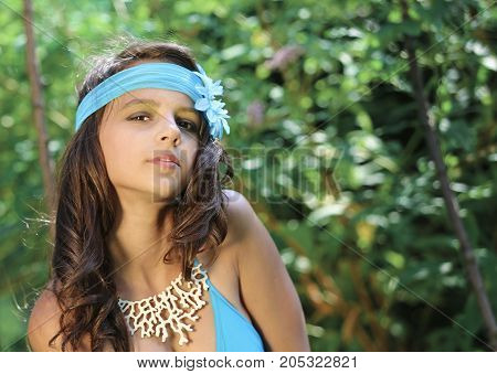 Beautiful brunette with long hair posing near bungalowk. Summer vacation concept.