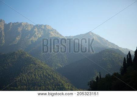 beautiful high mountains with a green summer landscape in clear sunny weather with a blue sky