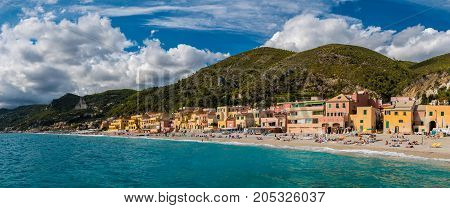 Panoramic view of Varigotti small sea village near Savona with crowded beach during a sunny afternoon