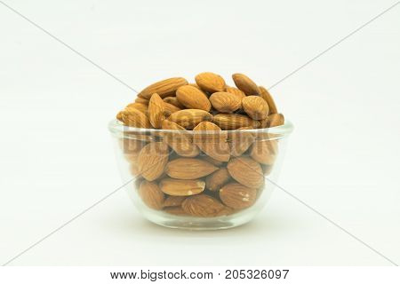 Glass cup of brown almond nut on white background