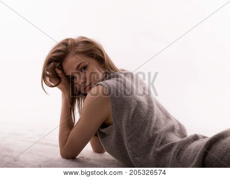 Tired sad woman during menstrual period lay on floor bed