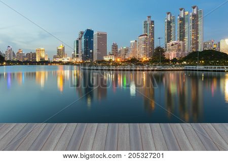 Opening wooden floor Night reflection of office building in public park cityscape downtown background