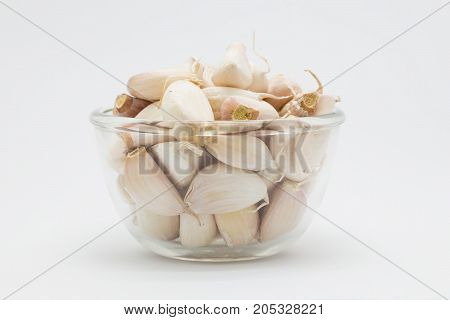 Fresh garlic in glass cup on white background