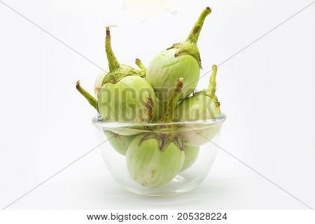 Green eggplant on glass bowl on white background
