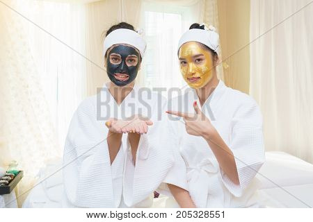 Beautiful young Asian woman having high quality and authentic pure gold facial mask and pointing her finger to her friend who having facial mud mask and open her hands for concept placing a sign or object on hands in spa salon