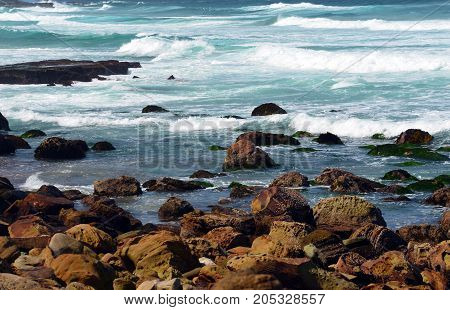 Waves crashing over sandstone rocks and platforms on NSW coast at Garie Beach, Royal National Park, Sydney