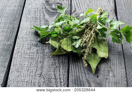 Bouquet garni. Classical french composition. Bay leaf parsley and thyme bound with culinary thread. Bunch of fresh aromatic herbs on dark wooden table