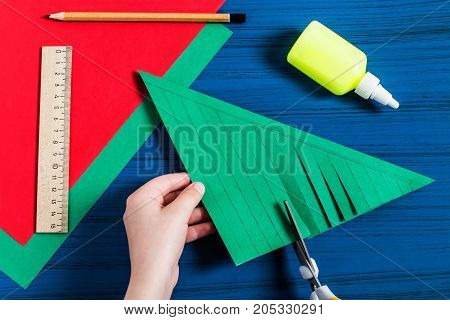 Making three-dimensional Christmas tree from paper to decorate room. Original children's art project. DIY concept. Step-by-step photo instructions. Step 4. Child cuts strips along drawn lines