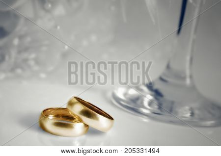 Gold wedding rings and focal on a light background. Allocation of rings in color. Blackout at the edges. Horizontal format. Indoors. Without people. Photo.
