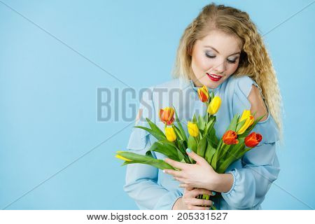 International women day eight march. Beautiful portrait of pretty woman blonde hair with red yellow tulips fashion make up elegant dress. Mother day. On blue