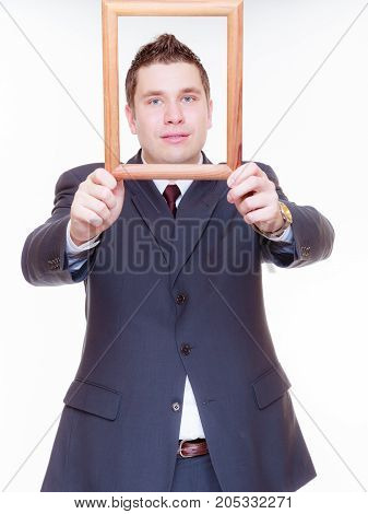 Looking good concept. Business man wearing elegant suit with face in wooden frame