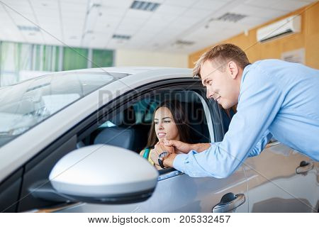 The young man came to the auto show to buy a new car. The concept of buying a new car.