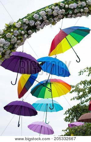 Bright umbrellas in festive decoration of city. Hanging multicolored umbrellas in sky above street. Avenue of flying umbrellas. Mood of joy and happiness. Selective focus. Vertical