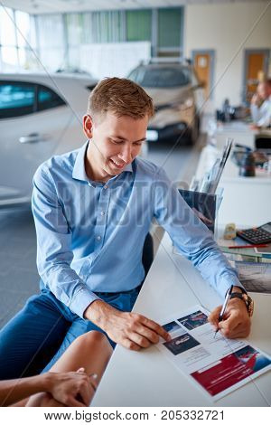 Young couple reading documents to buy a new car in the car dealership. The concept of buying a new car.