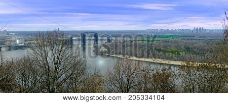 Bridge in Kyiv, fall view panorama on Dnipro river, Ukraine with a blue sky