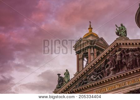 The bell tower of a beautiful church in silhouette against a colorful sunset sky with details visable including statues