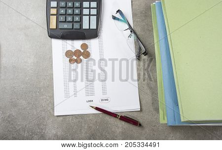 Profit and loss concept image of a pen calculator and coins on financial documents.