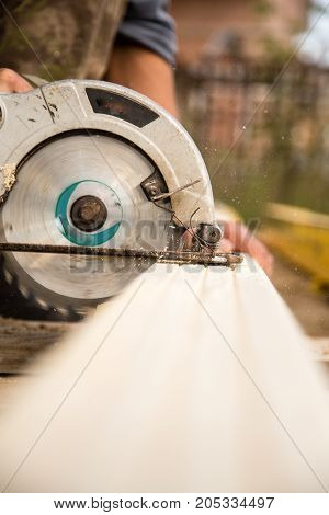 worker saws a wooden plank at a construction site .