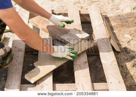 worker working with wooden planks at construction site .