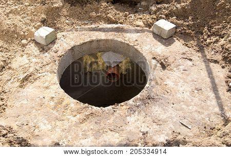 An open concrete drainage hatch near the house .