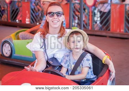 Mother and child riding an amusement park bumper car in the attraction park.