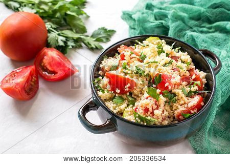 Bowl with couscous vegetables and herbs on pale gray background with green gauze napkin. Traditional food in cuisine of Maghreb. Vegetable ingredients: tomatoes and parsley. Dietary and healthy food