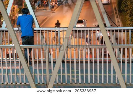 Asian man standing behind and holding a beer can on the footbridge and looking at the car run on the street, in the city night time.