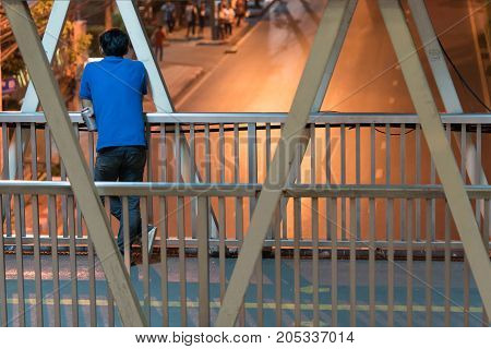 Asian man standing behind and holding a beer can on the footbridge and looking at the empty street not running cars, This is night time in the city of Bangkok.