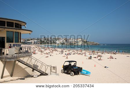 SYDNEY,NSW,AUSTRALIA-NOVEMBER 21,2016: Tourists at Bondi Beach with lifeguard tower and rescue vehicle in Sydney, Australia.