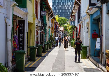 SINGAPORE - SEPTEMBER 7 2017: Shoppers walking along famous Haji Lane in Kampong Glam's muslim enclave where fashion boutiques eclectic collection of trendy stores and Middle Eastern cafes abound in old colonial shop houses.